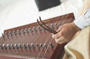 A santoor player holding the mallets used to strike the strings