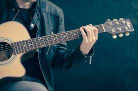 A man singing songs to learn to sing and play guitar