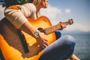 girl singing and playing guitar on beach