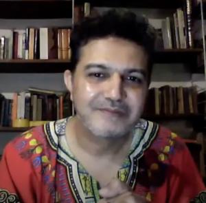 Arieb Azhar in front of a book shelf